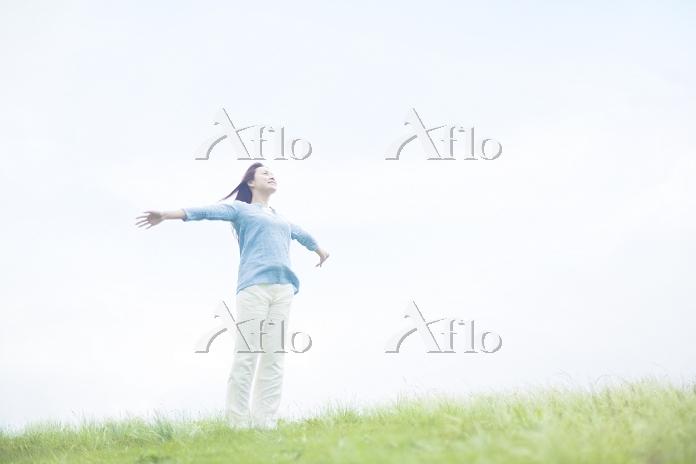 草原に立ち手を伸ばす若い日本人女性