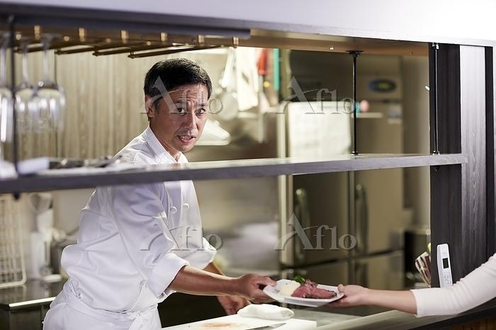 店員に料理を渡す日本人シェフ