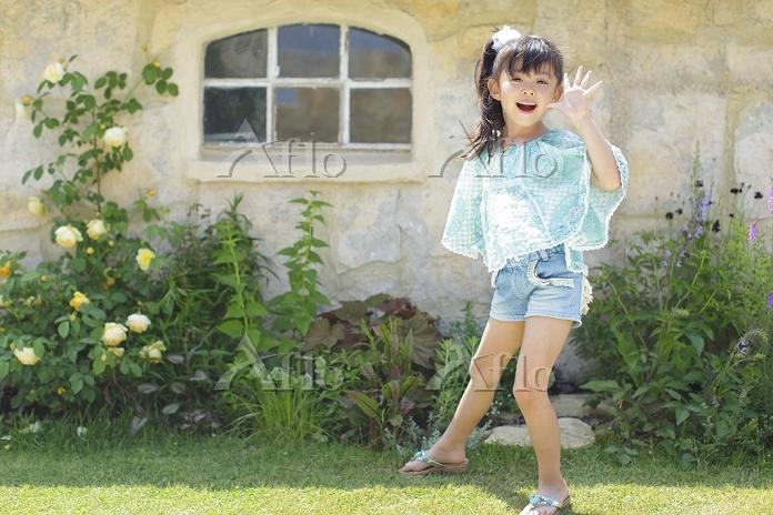 バラの咲く庭にいる日本人の女の子