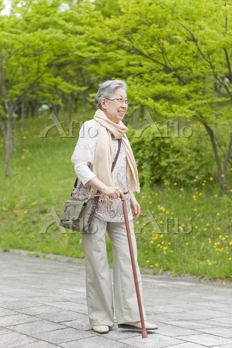 公園を散歩する杖をついたシニア日本人女性