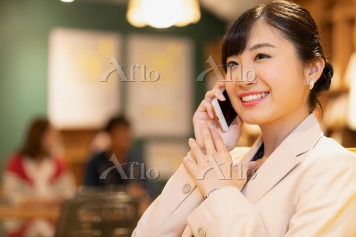 スマートフォンで通話する日本人ビジネスウーマン
