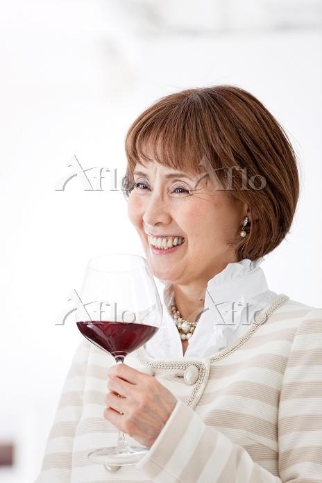 笑顔でワインを持つ中高年日本人女性