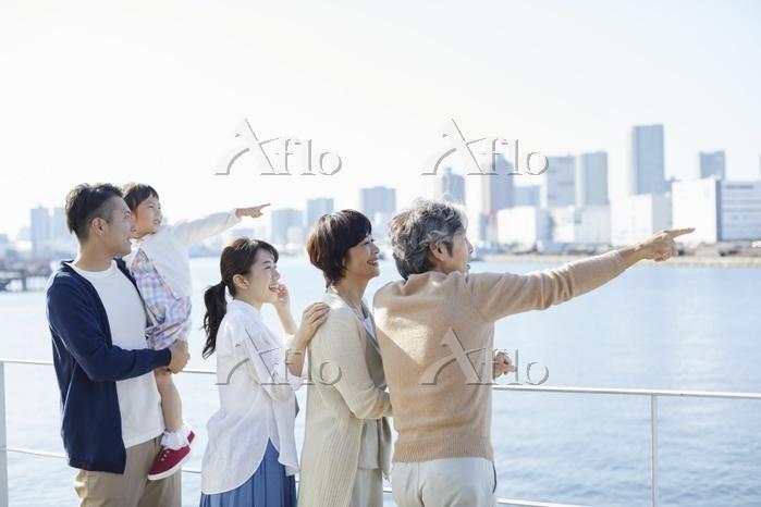 テラスで遠くを眺める日本の三世代家族