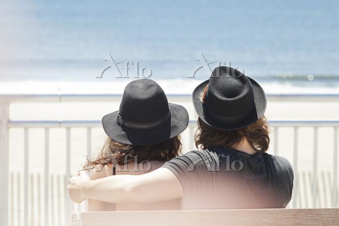 海を眺める若いカップルの後ろ姿