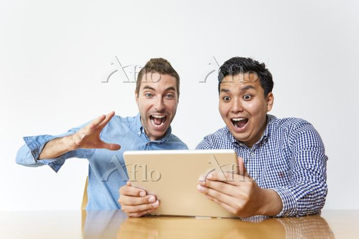 タブレットPCで応援する日本人と男性
