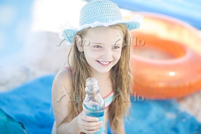 ビーチで水を持って笑顔の女の子