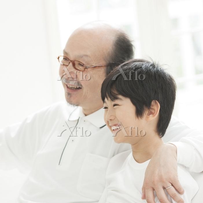 肩を抱いて笑う祖父と孫