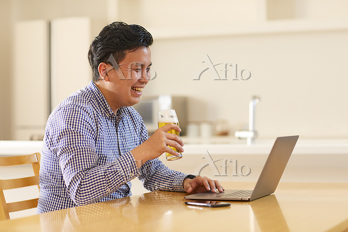 PCでオンライン飲み会を楽しむ日本人の若者