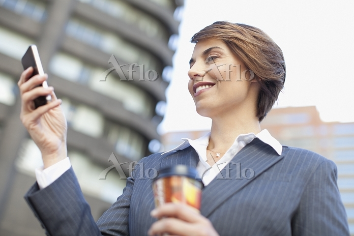 Businesswoman using cell phone・・・