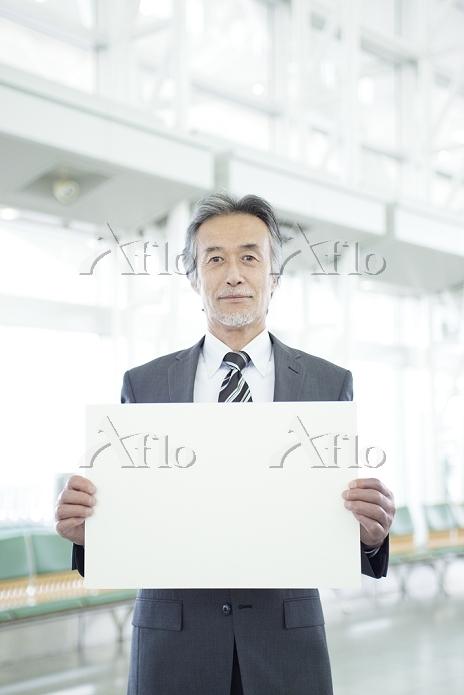 メッセージボードを持つシニアビジネスマン