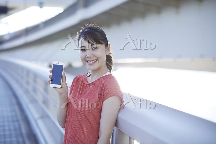 スマートフォンを持つランニングウェア姿の日本人女性