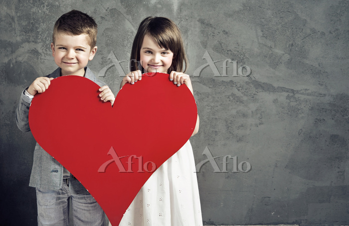 Smiling kids holding a toy hea・・・