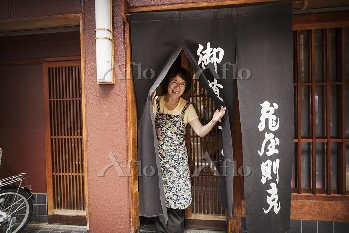 暖簾をわけて顔をのぞかせる日本人女性
