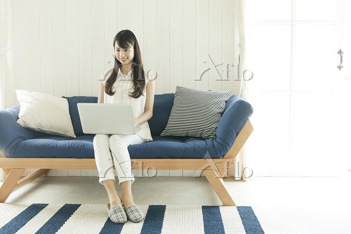 ソファに座ってパソコンを操作する若い日本人女性