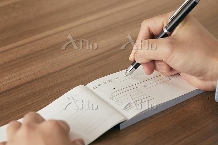 領収書とペンを持つ手