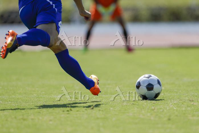 シュートを打つサッカー選手とキーパー