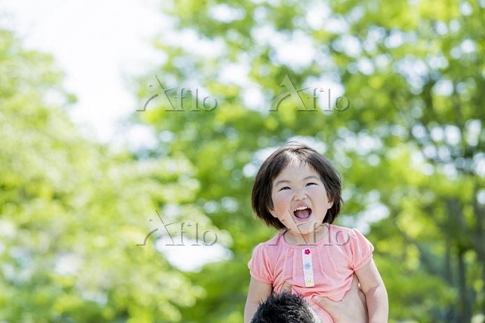 新緑の公園で遊ぶ父親と娘