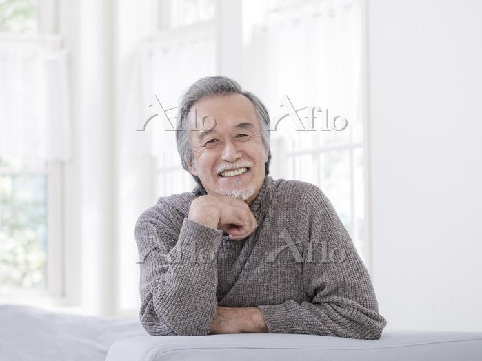 ソファで頬杖をつくシニアの日本人男性