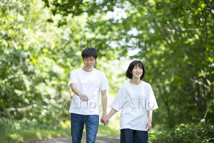 自然の中を手をつないで歩くカップル