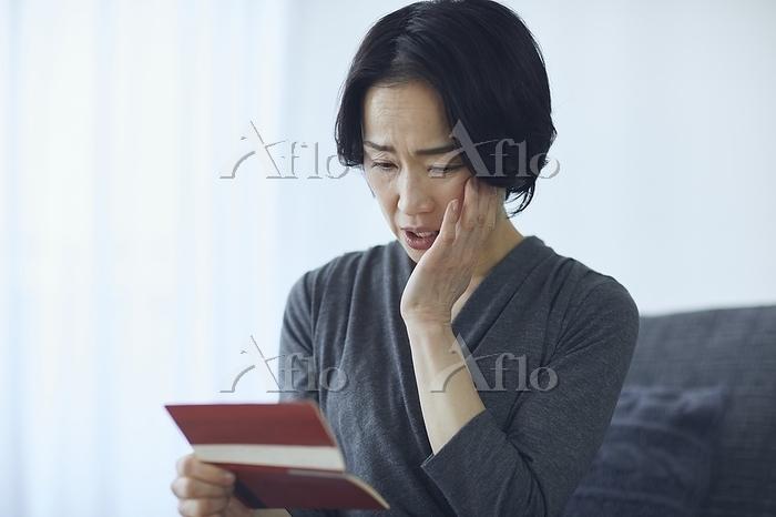 通帳を見るシニアの日本人女性