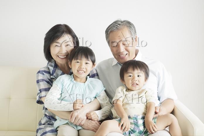 ソファに座る孫と笑顔の祖父母