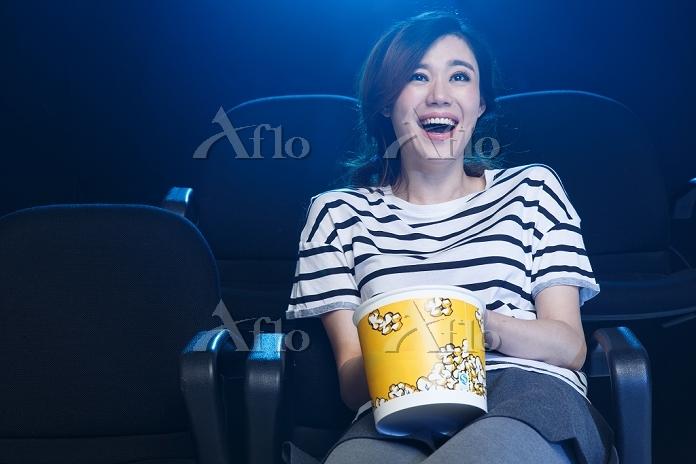 映画館でポップコーンを食べる女性