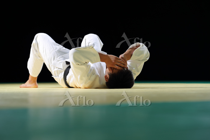 畳の上に横たわる男子柔道選手