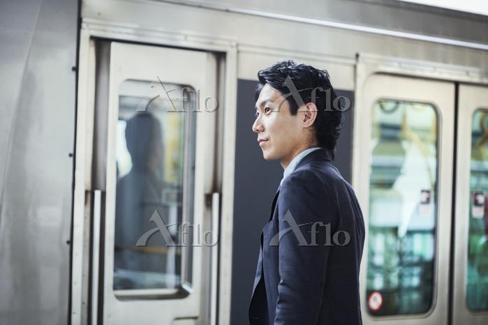 電車を待つ日本人ビジネスマン