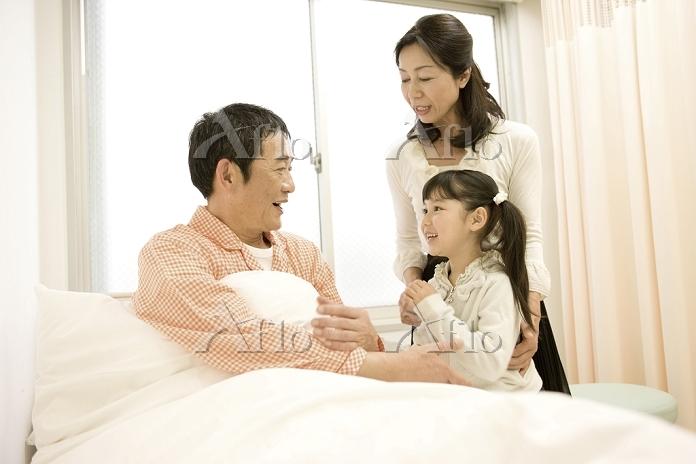 病室で夫を見舞う妻と子供9