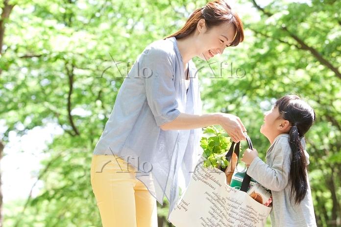 買い物袋を持つ母娘