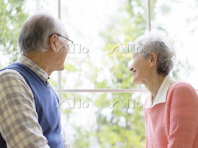 窓辺から遠くを見る日本人シニア夫婦