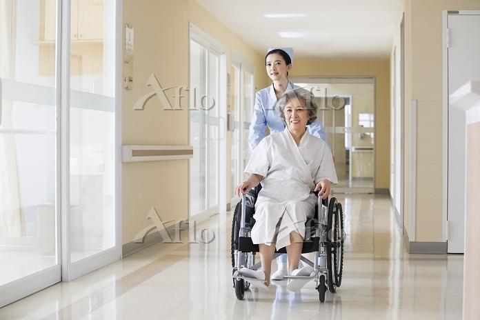 車いすで移動するシニア女性と看護婦