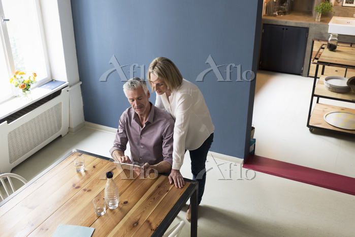 Mature couple using tablet at ・・・
