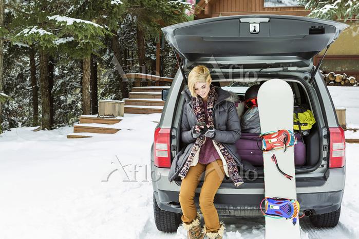 車でスノーボードをしに行く女性