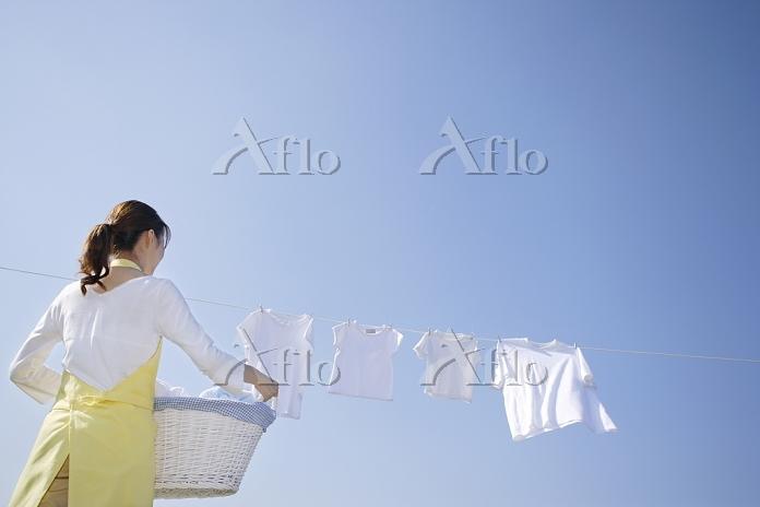 青空の下で家族の洗濯物を取り込む日本人女性