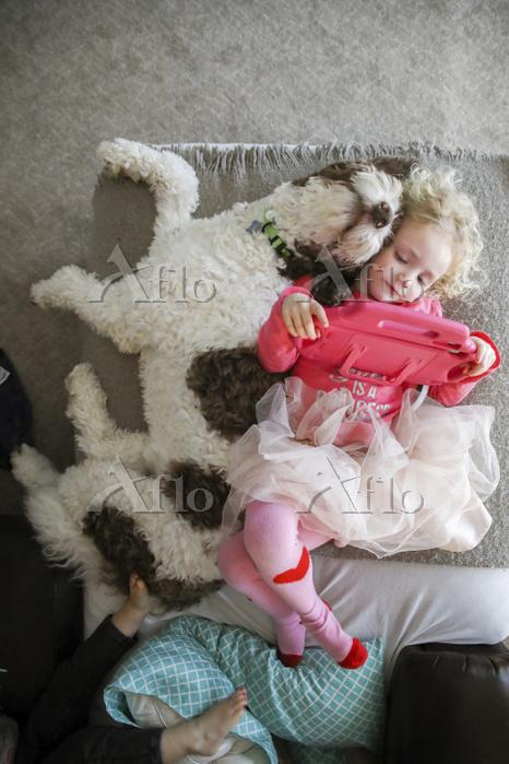 ベッドで眠る外国人の女の子と犬
