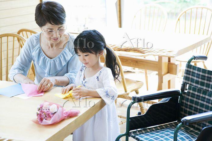 介護施設で孫と折り紙を折るシニア女性