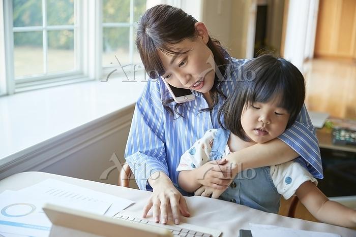電話をしている日本人の母親