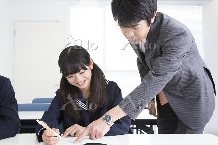 勉強する女子中学生と指導する講師