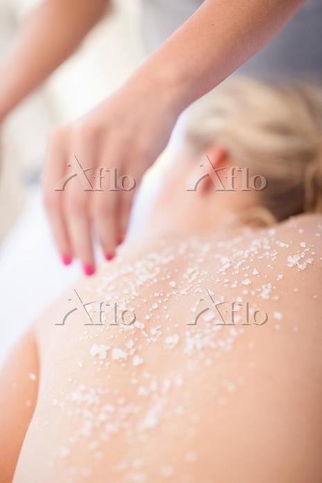 Woman having salt scrub on bea・・・