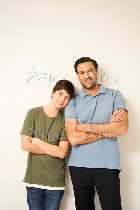 Boy and father with arms folde・・・
