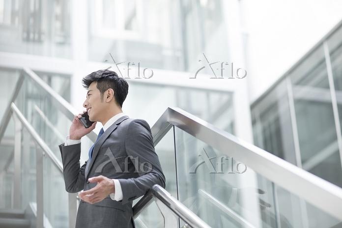 階段で電話をするビジネスマン