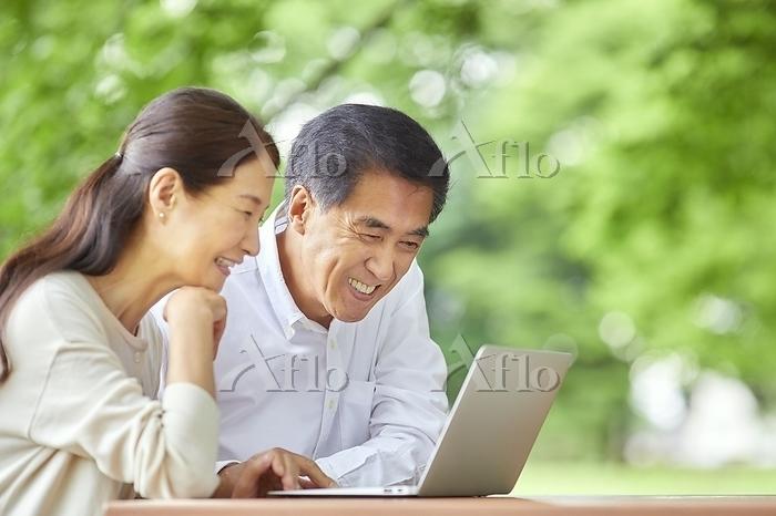 ノートパソコンを見る日本人シニア夫婦
