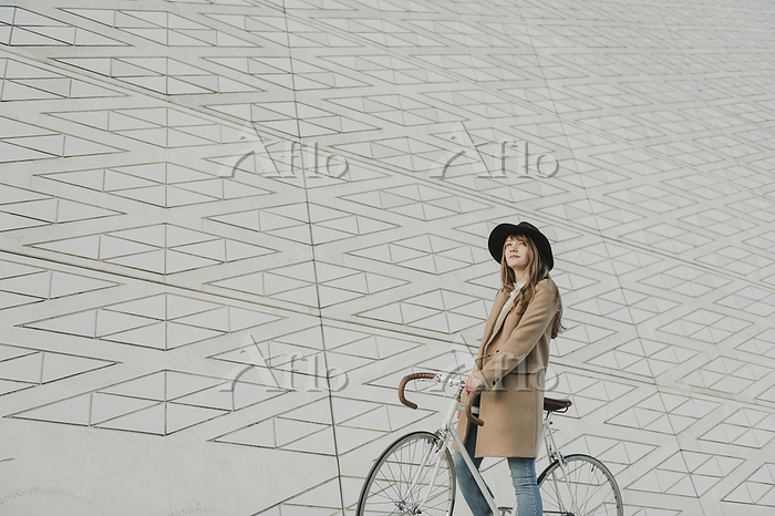 Young hipster woman on a bicyc・・・