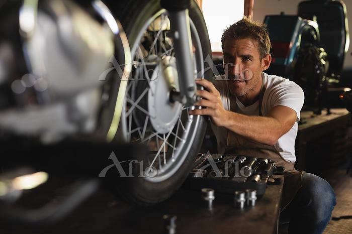 オートバイを修理する男性