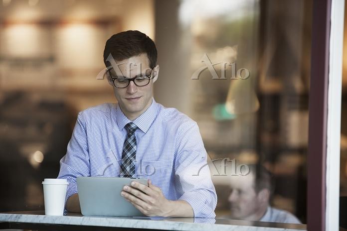 カフェでタブレットを見るビジネスマン