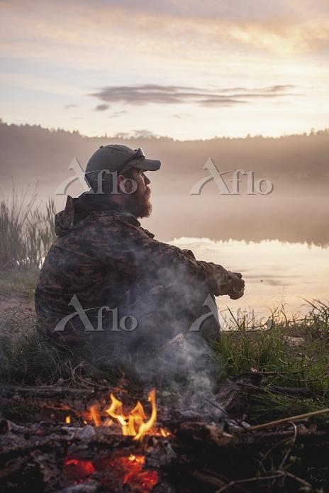 日没を見ながら焚火をするハンター