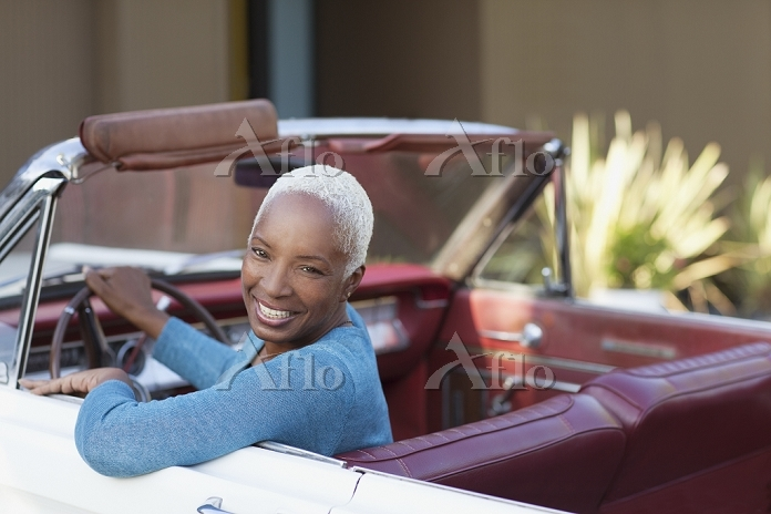 Smiling older woman driving co・・・