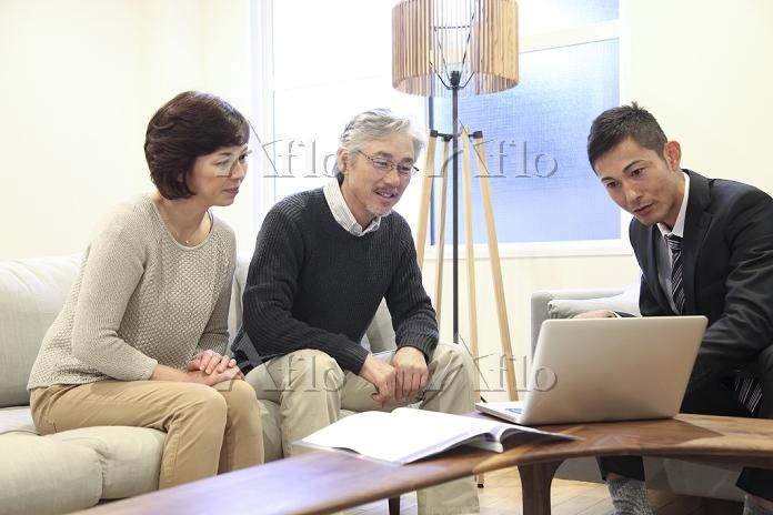 ビジネスマンの説明を受けるミドル日本人夫婦