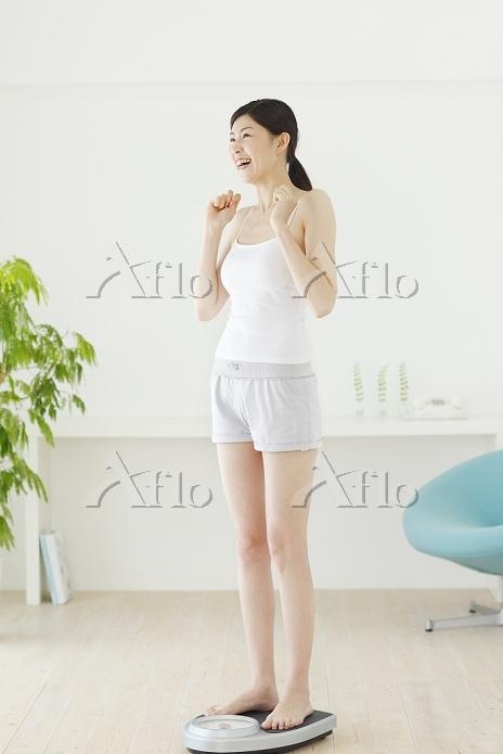体重計に乗る若い日本人女性